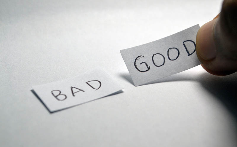 Mano con dos tiras de papel de Bad y Good